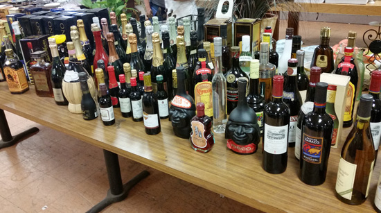 A table of wine and liquor waiting to be sold at auction.