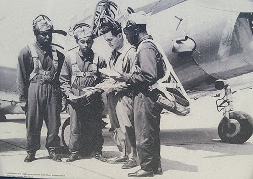 Cadets and their instructor go over flight procedures at Tuskegee Army Air Field. Photo from a board at Moton Field.