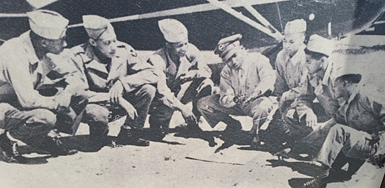 Cadets watch as their pre-flight instruction explains a maneuver, 1941. This photo is on one of the boards at the Moton site.