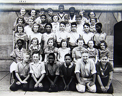 Elementary school photo. The boy on the bottom row right has tattoos on his arm.