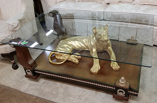 Glass-topped coffee table with a lion in gold-leaf.