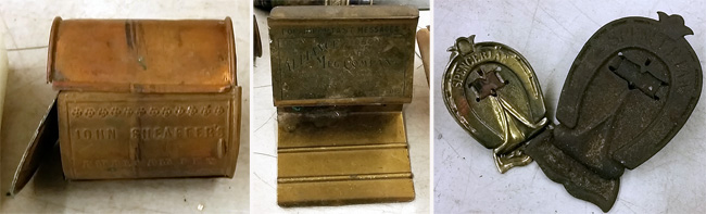 Desk accessories: from left, a brass box marked John Sheaffer's; center, message holder; right, oversized paper clips.