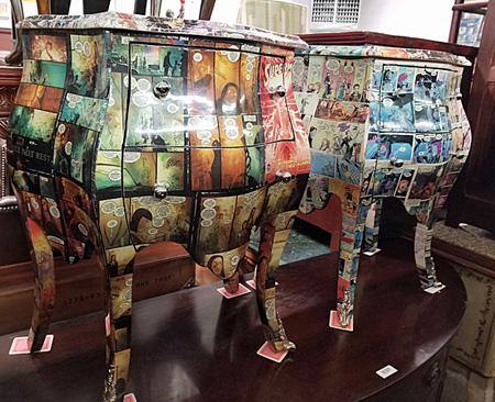 A pair of chests, or commodes, with decoupage comics at auction.