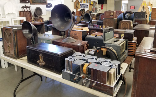 A collection of radios and accessories fill tables at the auction.